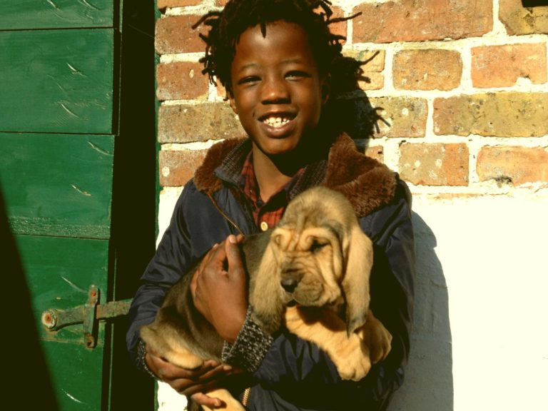 Emile houdt een pup in zijn armen naast een groene poort
